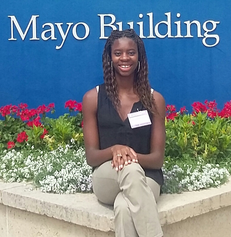 Biology student sitting in front of Mayo Clinic sign