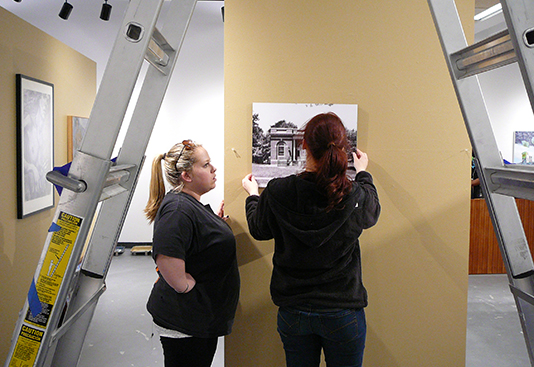 Students hanging work in gallery