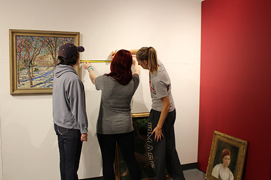 Making Her Mark Exhibition - image of students installing painting